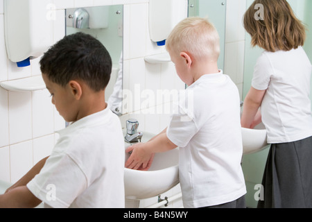 Students in bathroom at sinks washing hands - Stock Photo