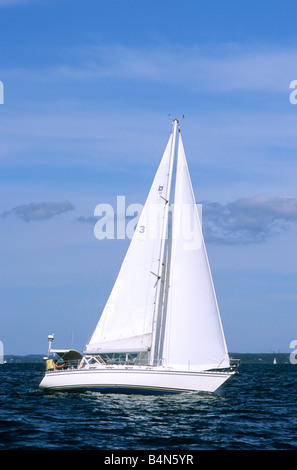 White sailboat sailing off Cape Cod under full sail main and jib - Stock Photo