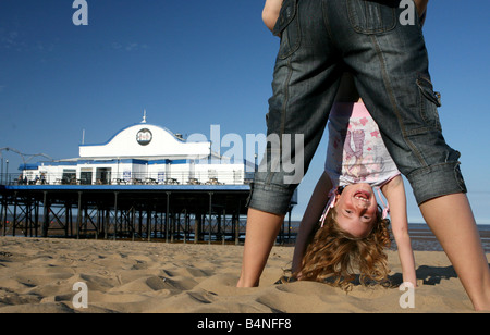 Girl and mother playing on the beach at Cleethorpes near Grimsby Humberside north east Lincolnshire holiday fun - Stock Photo