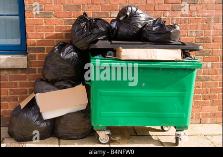 Overfull green trashcan - Stock Photo