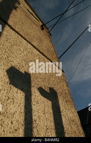 two footpath signs shadow on house wall in sun - Stock Photo