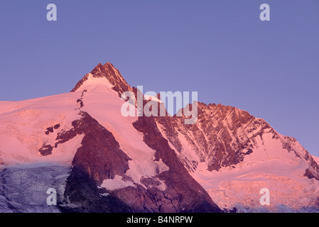 Alpenglow over Grossglockner with climbers on trail near summit in Hohe Tauern National Park Alps Carinthia Austria - Stock Photo