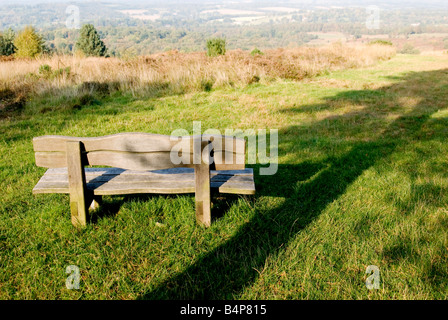Wooden bench looking out over the Ashdown Forest, with a shaddow of a tree beside of the bench - Stock Photo
