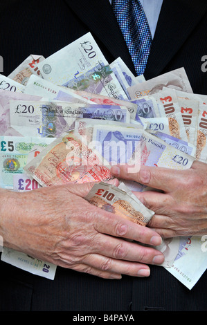 Man wearing office business suit with hands clutching piles of money concept for bankers, fatcats, greed, Men in - Stock Photo