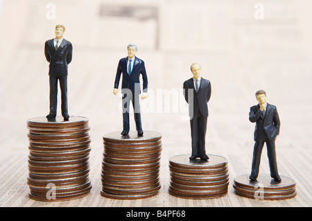 Figurines of businessmen standing on piles of coins - Stock Photo