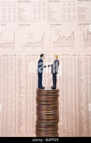 Figurines of businessmen shaking hands on piles of coins against financial newspaper - Stock Photo