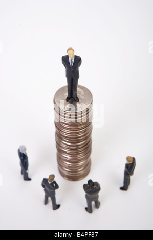 Male figurine standing on top of stacked coins - Stock Photo