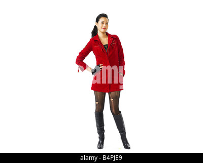 Portrait of a young woman standing with hand on hip against white background - Stock Photo