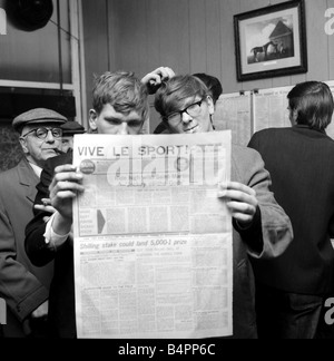 Punters studying the form guide in a French newspaper before placing their bets on the race at Saint Cloud at George - Stock Photo