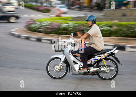 Thailand Transport; thailand family motorcycle child passenger bike scooter traffic in Pattaya. - Stock Photo