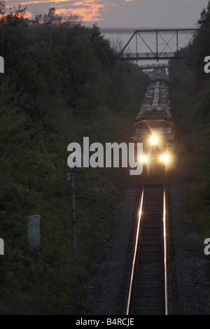 Approaching Freight Train at Sunset Under Truss Bridge Ontario Canada - Stock Photo
