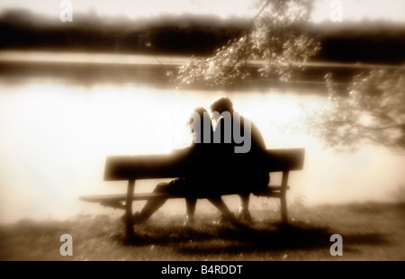 two people on a park bench silhouetted against a lake in sepia tones - Stock Photo