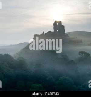 Corfe Castle at sunrise on summer morning from West Hill Dorset England UK - Stock Photo