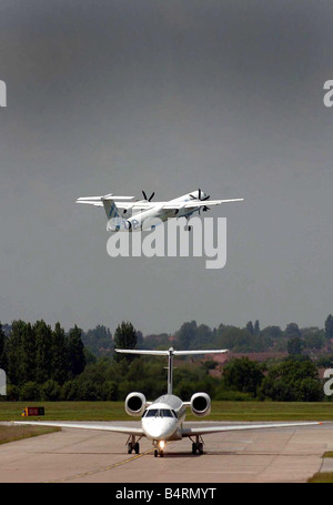 A Flybe short haul commuter aircraft takes off from Birmingham airport as a Executive Jet taxi s on to the apron - Stock Photo