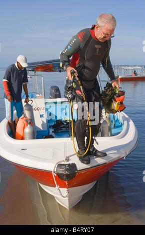A diver returning to Mabul Island after diving around Sipadan Island nr Semporna Sabah Malaysia - Stock Photo