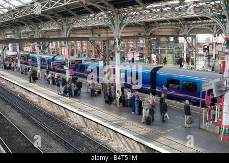 local commuter diesel train and people standing on the platform Preston railway station, Lancashire England UK - Stock Photo