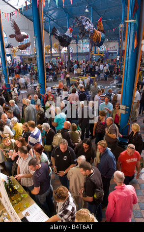 Crowds of people wander sit and browse stalls ain Market Hall at Abergavenny Food Festival - Stock Photo