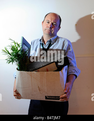 Man packs up and leaves the office after losing his job, being made redundant, being fired - Stock Photo