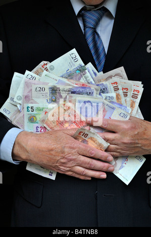 Model released man wearing office business suit hands clutching piles UK pound notes money concept for bankers, - Stock Photo