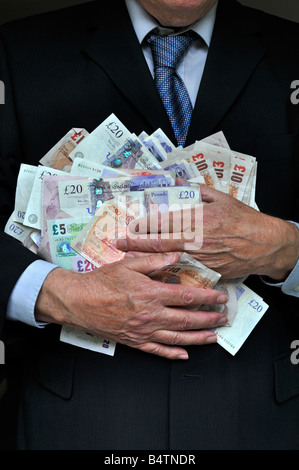 Man wearing office business suit hands clutching piles of money (concept for bankers, fatcats, greed, Men in Suits) - Stock Photo