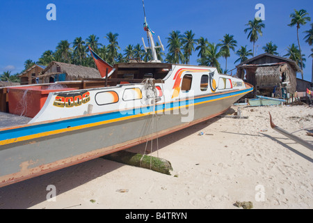 A fishing boat pulled up onto the beach in front of a fishing village on Mabul Island nr Semporna Sabah Malaysia - Stock Photo