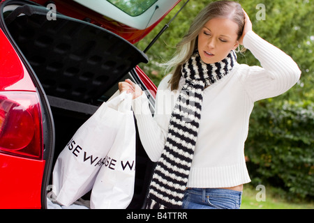 Girl looking depressed with shopping bags - Stock Photo