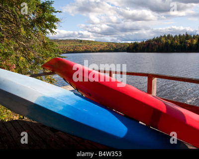 A red and blue kayak on a dock with fall colours around them on the st john river new brunswick canada - Stock Photo