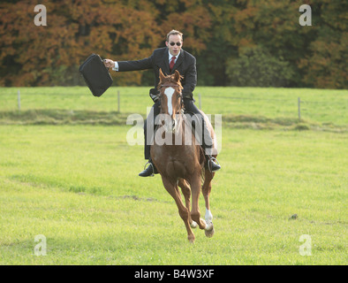 Young businessman riding a horse at full gallop holding up a case - Stock Photo