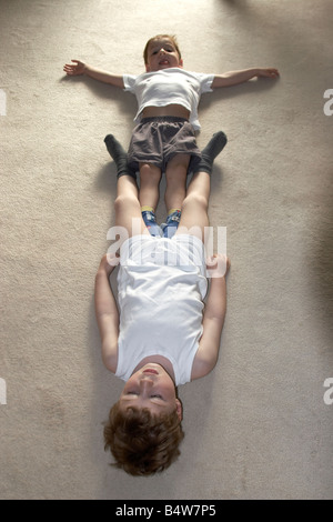 Two young boys lying on the carpet playing upside down wearing vests and socks smiling to camera NAOH CJWH - Stock Photo