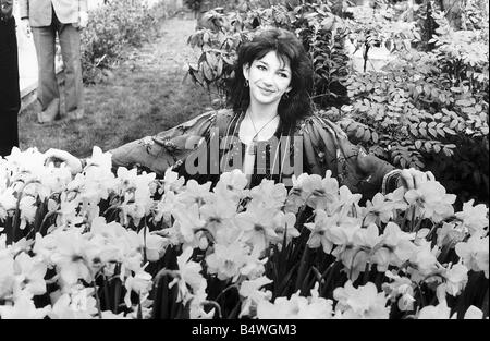 Pop singer Kate Bush poses in a garden full of daffodils and trees December 1979 - Stock Photo