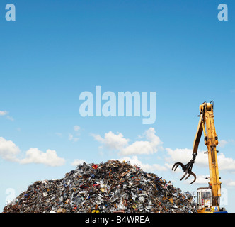 Mechanical grabber and scrap heap - Stock Photo