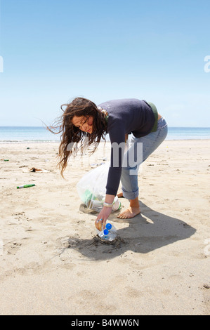 Young girl collecting garbage on beach - Stock Photo