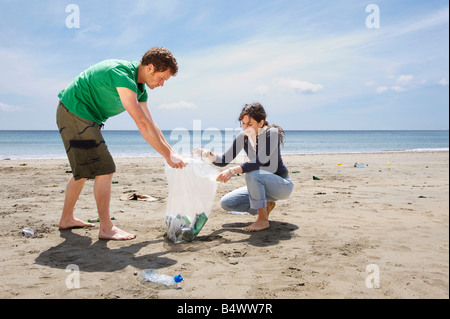 Young couple collecting garbage on beach - Stock Photo