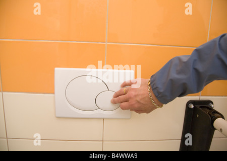 Close up of a female hand pressing the low flush button of a dual flush toilet - Stock Photo