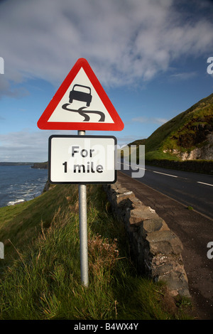 slippery road danger red warning triangle for 1 mile sign on the famous A2 north antrim causeway coastal road route - Stock Photo