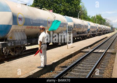 Signalman waving green flag Signal for freight train, signals and signaling, signalling at Hua Hin, Railway Station, - Stock Photo