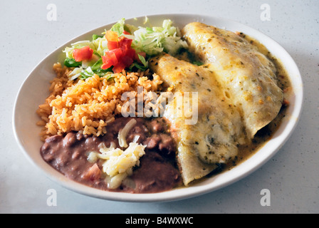 Swiss enchiladas filled with chicken and sour cream served with rice and beans with cheese and chopped salad - Stock Photo