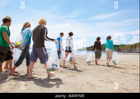 Young people collecting garbage on beach - Stock Photo
