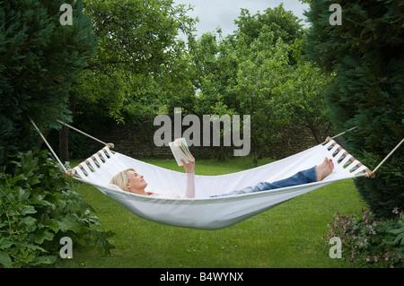 Woman relaxing in hammock in garden - Stock Photo