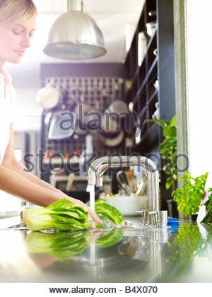 Woman in kitchen washing food - Stock Photo