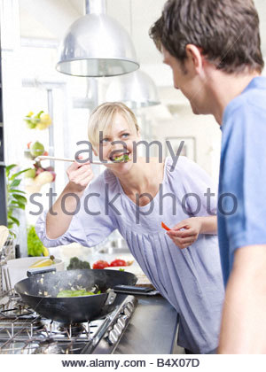 Man and woman in kitchen cooking food - Stock Photo