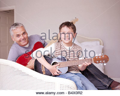 Father and son on bed with guitar - Stock Photo