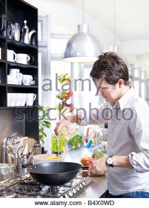 Man in kitchen cooking with wok - Stock Photo
