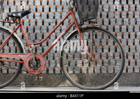 Old women's bicycle leaning against a tiled wall. - Stock Photo