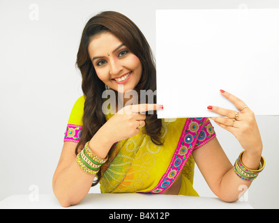 a pretty asian woman of indian origin in a traditional dress with a blank placard - Stock Photo