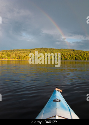 Cloudy summer day on the St John River in New Brunswick with a double rainbow over the hills - Stock Photo