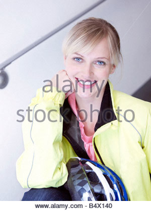 Woman sitting by window on stairs - Stock Photo