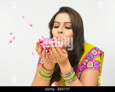 asian woman of indian origin blowing rose petals held in her plam - Stock Photo
