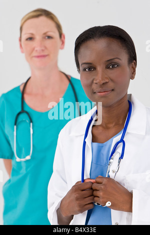 A female African American doctor with her colleague out of focus behind her - Stock Photo