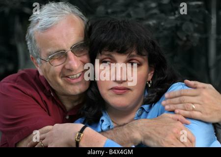 Mature man embracing his upset wife - Stock Photo